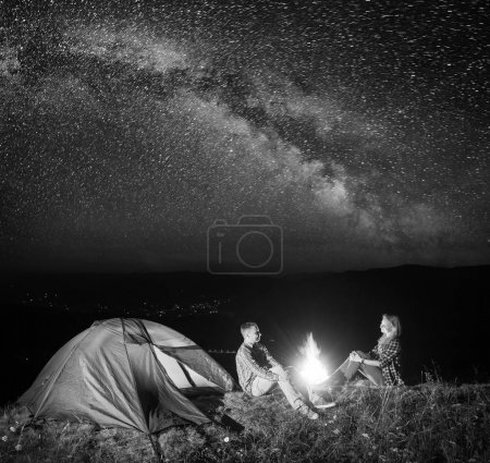 Night tent camping. Young couple hikers sitting near fire under incredibly beautiful starry sky and Milky way. In the background luminous village in the valley. Black and white