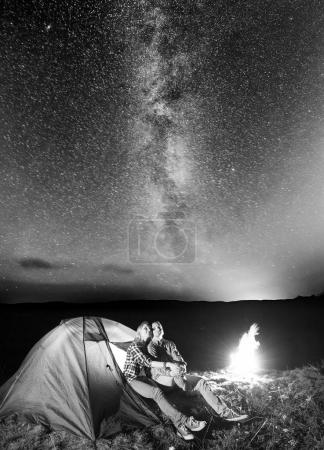 Young pair hikers looking to the shines starry sky