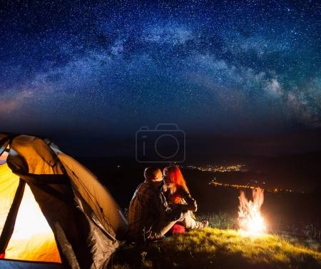 Night camping. Charming pair tourists