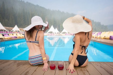 Rear view of two women in a hats sitting
