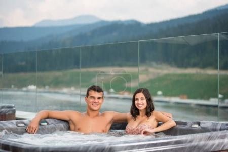 Young couple relaxing enjoying jacuzzi hot tub