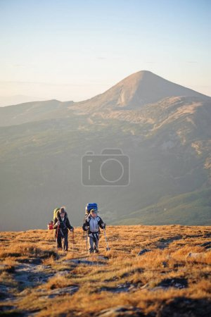 Couple hikers in the Carpathians mountains with backpacks