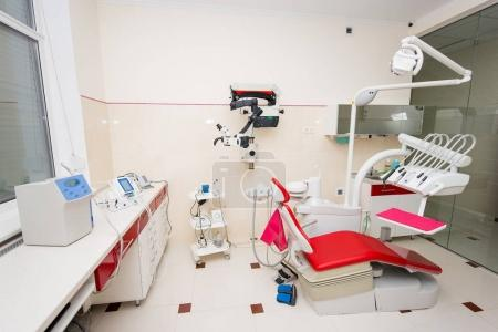 Denatal chair and modern dental equipment in red and white dental clinic room