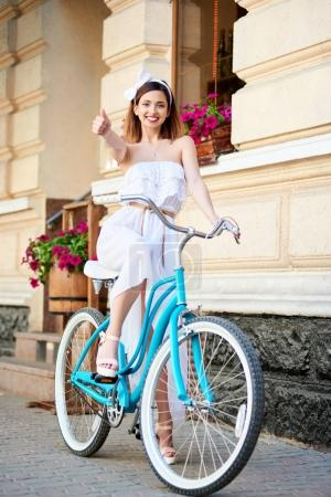 cute woman in white summer dress and bow on head showing thumb up while standing with blue retro bicycle in old city