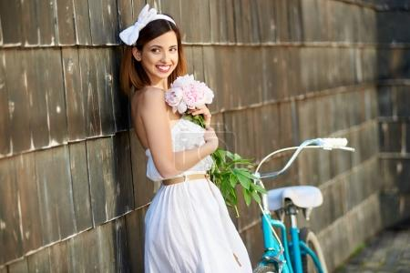 happy young beautiful woman holding bunch of peonies posing elegantly near bicycle outdoors
