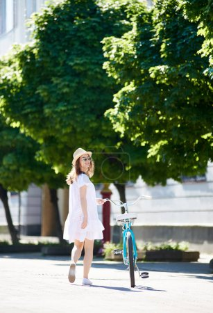 Lonely girl comes with a retro bicycle on the sunny city street