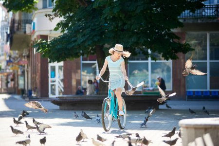 Positive young girl in straw hat riding blue vintage bike in paved city center chasing pigeons flocks during hot summer day.