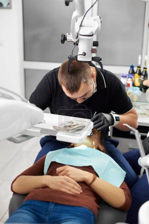 Dentist is treating the patient's teeth by bending over her in a clinic. He wears a black mask, gloves and uniform. Modern dentistry with the use of new technologies