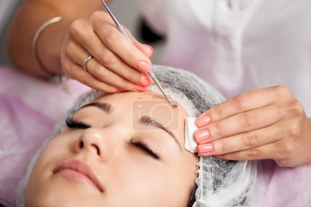 Female client is having facial treatment with the help of eye loop. Cosmetology and skin care routine.