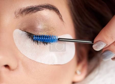 Beautiful woman with long eyelashes in a beauty salon. Eyelash extension procedure. Lashes close-up