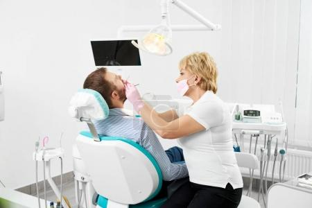 Female dentist in mask with mirror checking patient man teeth up at modern dental clinic office
