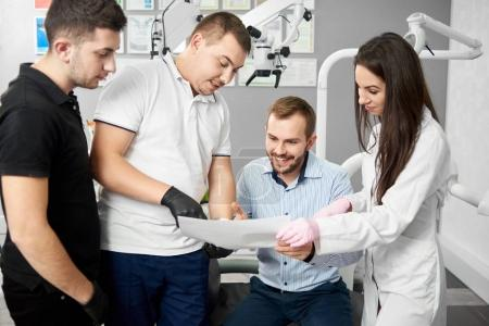 Two male dentists and their attractive female assistant are showing the paper to a satisfied smiling male client of the dental office.