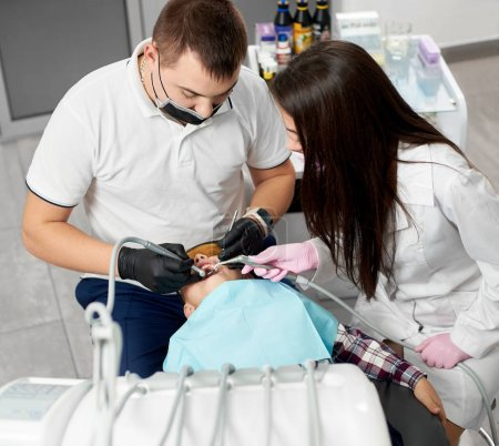 Dentist male with the assistant are treating cute little boy's teeth in modern clinic
