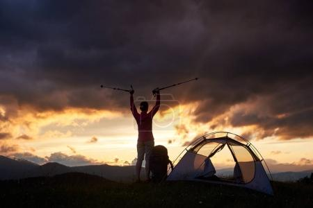 Reaching the top. Toned young female enjoying beautiful sunset with walking sticks in her hands near tent on top of mountain hill. Night evening tourist climber majestic amazing view scenery