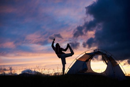 Silhouette of a woman doing yoga on top of a mountain on sunset near the tent copyspace harmony balance nature travelling tourism sports recreation happiness hiking backpacking.
