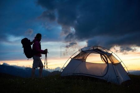 Silhouette of female tourist near the tent with backpack on her shoulders and walking sticks in hands enjoying sunset view over mountain hills. Travel and active way of life concept.