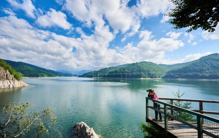 Photographer female on the lake Vidraru Carpathians Romania. Beautiful scenery of a sunny day: mountains, forests, lake, blue sky with clouds
