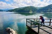"""Постер, картина, фотообои """"Молодая женщина фотограф с синий рюкзак на озере. Красивые пейзажи Солнечный день: горы, леса, озера, Голубое небо с облаками"""""""