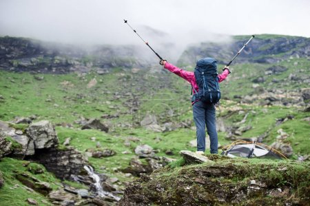 Rear view low angle shot of a female hiker with a backpack spreading her arms with trekking poles in victorious success gesture copyspace nature happiness harmony achievement leadership torism.