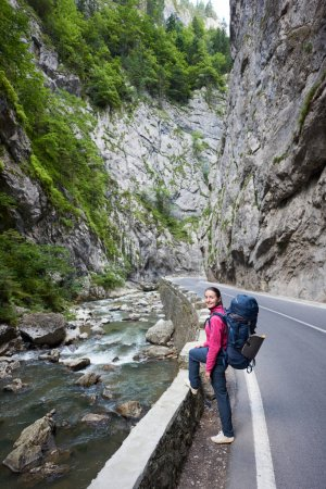 Pretty woman with backpack on road next to a mountain stream in the Bicaz Gorge. Canyon is one of the most spectacular roads in Romania-Carpathian Mountains.