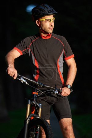 Smiling male standing cyclist near bike, happy to begin morning with training. Sportsman having fun exercising outdoors. Concept of healthy lifestyle, new beginning