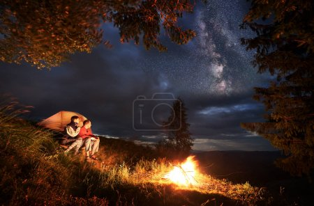 Camping at night. Young couple hikers sitting by the campfire and illuminated orange tent, looking into the distance under the evening sky. Through clouds on the sky are visible bright stars.