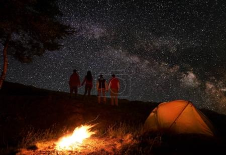 Back view of two pair hikers holding hands and enjoying milky way at starry sky during a night of camping near a campfire and orange tent in mountains. Romantic evening under the fabulous starry sky