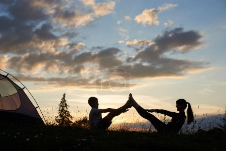 Silhouettes of woman and boy sitting on the grass with wildflowers and doing stretching at sunrise near the camping. Happy faces of mother and child while playing sports under the morning sky