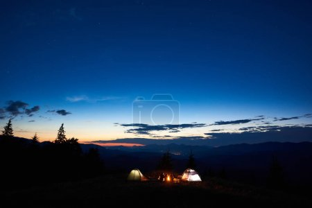 Silhouette of family hikers mother, father, two children enjoying at camping in mountains, beside campfire and two illuminated tents, under amazing view of evening sky, sunset, stars