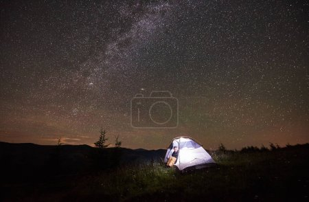Happy girl traveller having a rest at night camping in the mountains under incredible beautiful starry sky and Milky way. Smiling woman sitting inside illuminated tent and looking at sky full of stars