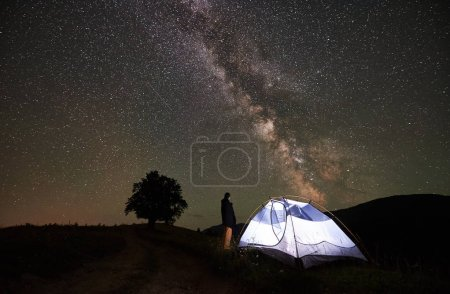 Female tourist enjoying incredible beautiful starry sky and Milky way at night camping in the mountains. Woman standing beside illuminated tent. Silhouette of big tree on background.