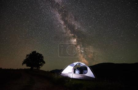 Woman traveller resting at night camping in the mountains. Rear view of girl hiker sitting inside illuminated tent, enjoying view of incredible beautiful starry sky and Milky way. Astrophotography