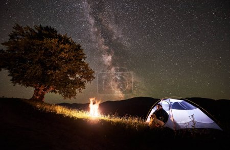 Woman backpacker resting at night camping in the mountains under amazing night sky full of stars and Milky way. Girl hiker sitting inside illuminated tent near campfire and big tree. Astrophotography