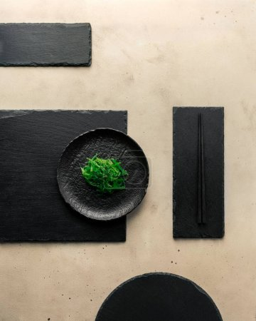 Photo for Stylishly arranged chuka seaweed salad, black sesame seeds on black slate plates of different shapes. Top view, vertical orientation - Royalty Free Image