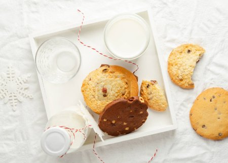 Photo for Selection of homemade cookies, milk, winter decor on white wooden tray on white background, top view, horizontal orientation - Royalty Free Image