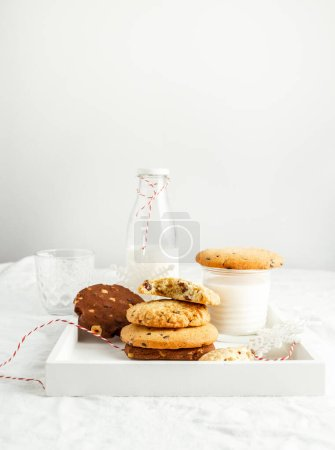 Photo for Selection of homemade cookies, milk, winter decor on white breakfast tray on white background. Vertical image with copy space - Royalty Free Image
