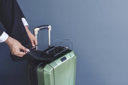 Photo pour Partie d'homme d'affaires soulever ses chaussures de cuir noir de formel sur un bagage et attacher le lacet à l'aéroport le plus pratique pour se préparer pour voyage d'affaires, vue latérale - image libre de droit