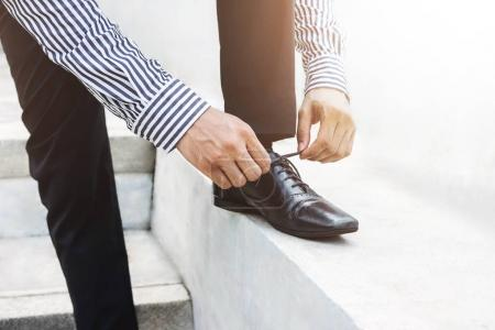 Photo for Businessman tie shoelace, Get ready for new challenge concept, Lower part and outdoor scene - Royalty Free Image