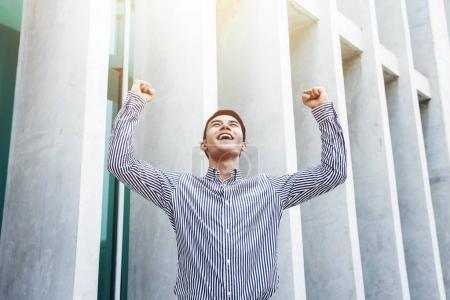 Photo pour Heureux homme d'affaires en posture gai, susciter des mains et grand sourire, succès et puissant dans le concept d'affaires - image libre de droit