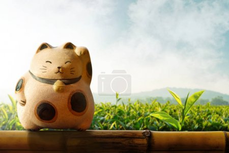 Photo pour Japon Maneki Neko ou chat, mascotte de chance et d'argent, présenter au cours de clôture de bambou et de plantations de thé vert comme toile de fond - image libre de droit