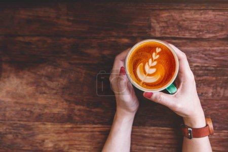 Foto de Taza de café Latte en mano Hipster mujer pone en la mesa de madera en Cafe, vista superior - Imagen libre de derechos