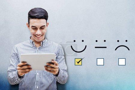 Photo pour Client expérience Concept, homme d'affaires heureux holding tablette numérique avec une case cochée sur le visage de Smiley excellente notation pour un questionnaire de Satisfaction - image libre de droit