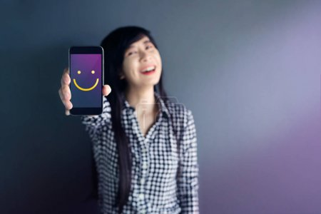 Customer Experience Concept, Happy Woman Show Excellent Rating with Smiley Face icon for her Satisfaction on Smart Phone