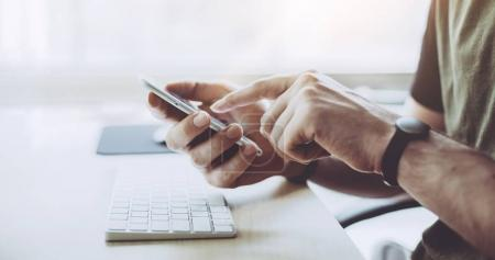 Photo for Man working on modern mobile phone at sunny office, Hipster man holding on hands modern mobile phone - Royalty Free Image