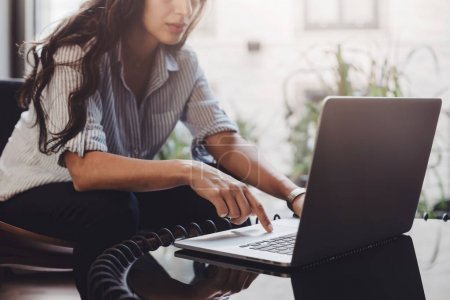 Business woman working on laptop in loft interior