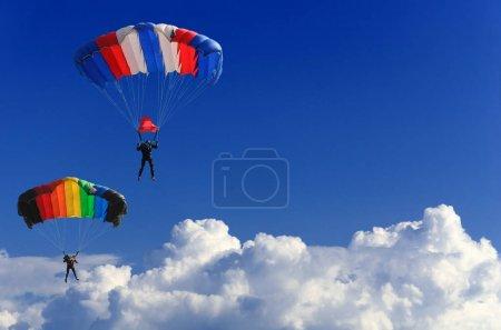 Photo pour Deux courageux parachutistes font un vol conjoint sur deux parachutes multicolores à travers le ciel bleu sans bornes - image libre de droit