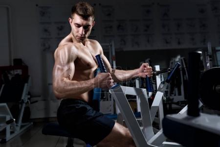 Photo pour Jeune homme musclé avec un torse nu, on s'entraîne dans la salle de gym - image libre de droit