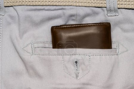 Brown leather purse in the pocket. Wallet halfway out from a jeans back. Pocket white jeans with Wallet brown color.