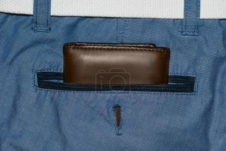 Brown leather purse in the pocket. Wallet halfway out from a jeans back. Pocket blue jeans with Wallet brown