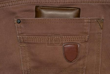 Brown leather purse in the pocket. Wallet halfway out from a jeans back. Pocket jeans with Wallet brown color